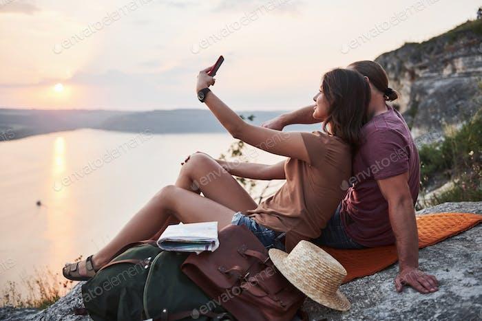 Umarmung Paar mit Rucksack sitzt auf der Spitze des Felsens Berg genießen Blick Küste einen Fluss oder See