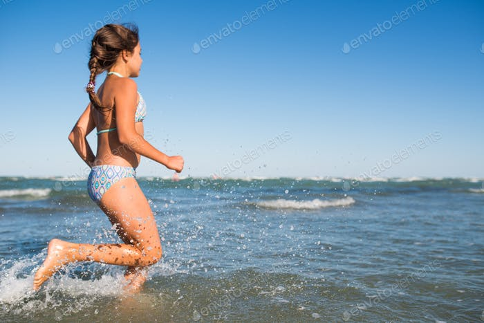 Portrait of a joyful little girl swimming in sea