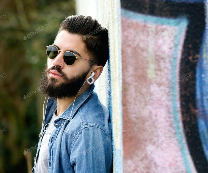 Modern young man with beard listening to music with earphones