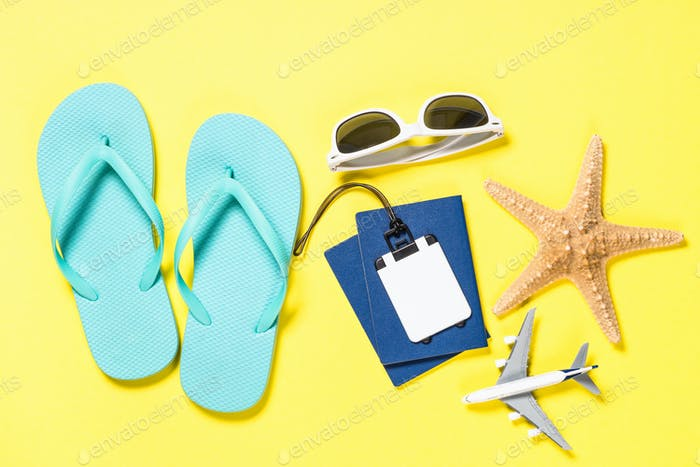 Blue flip flops, sunglasses, passport and starfish on yellow background