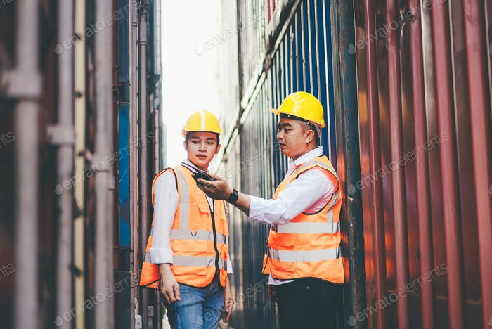 Asian container worker talking on walkie talkie to control  at warehouse