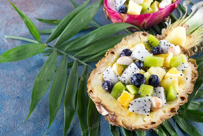 Exotic fruit salad served in half a pineapple on palm leaves on stone background. Healthy food