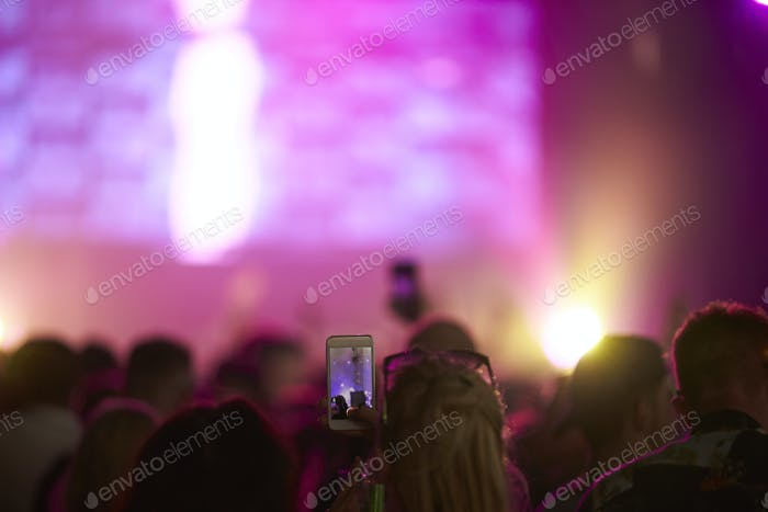 Fan Taking Photo On Mobile Phone At Music Festival