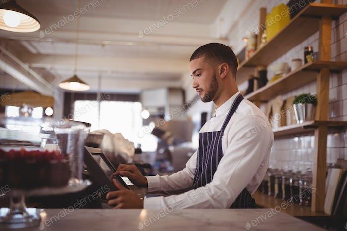 Seitenansicht der schönen jungen Kellner mit Computer am Schalter
