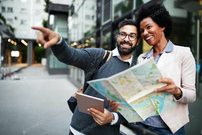 Lost happy couple in the city holding a map. Travel, tourism, people concept