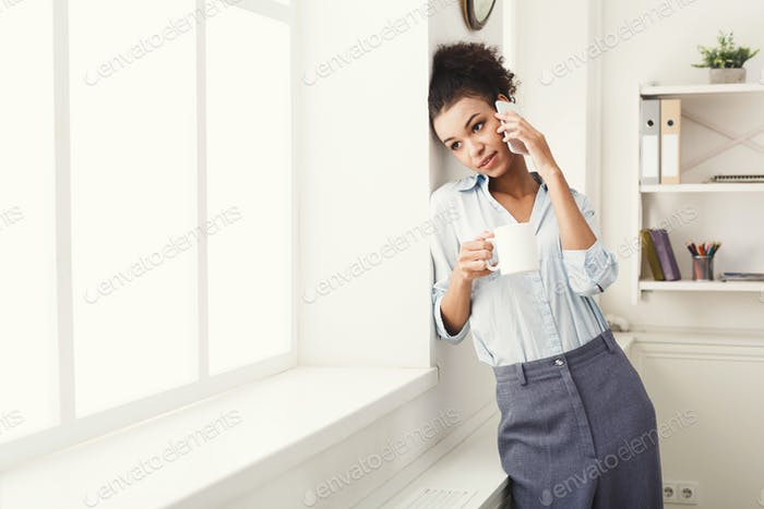 Business woman has phone talk near office window