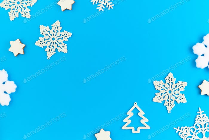 Flat layout of white decorative snowflakes and firtrees surrounding copyspace