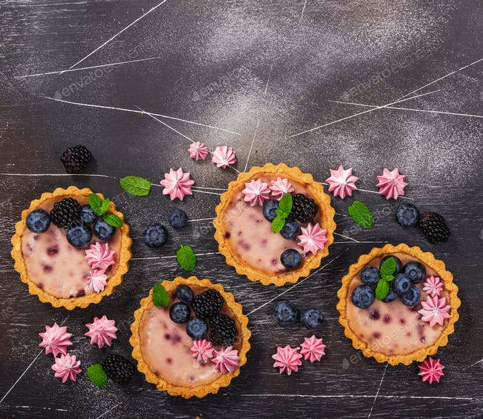 Four round shaped cheesecakes with fresh blackberries, blueberries, meringue and mint