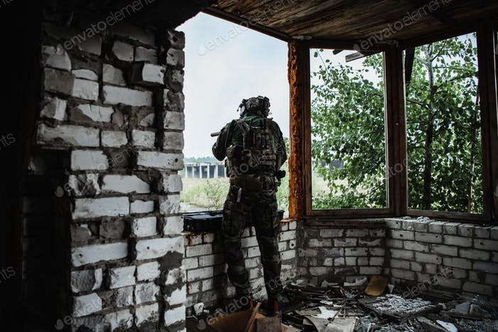 Military man with gun case takes out an assault rifle in destroyed city. Military and rescue