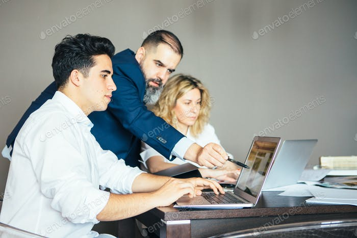 Three businesspeople at table with computers