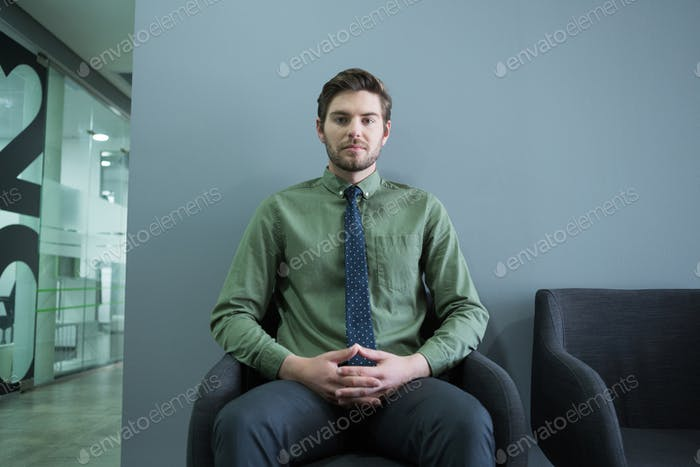 Confident executive sitting on chair in waiting area