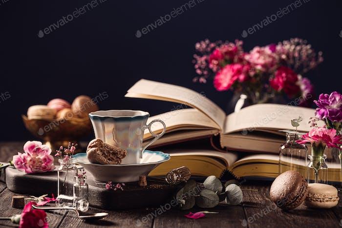 Tasse de café, vieux livres et fleurs d'oeillet rose
