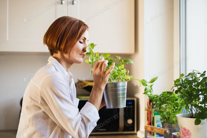 A young woman standing indoors in kitchen, smelling herbs.