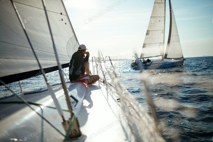 Junge gutaussehende Mann entspannt auf seinem Segelboot