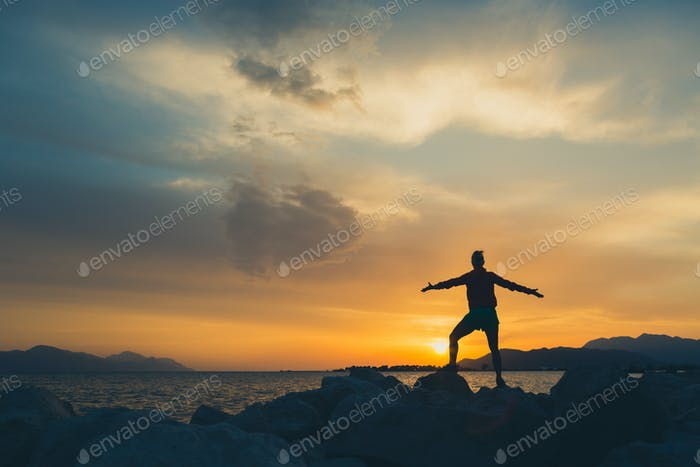 Woman hiker with arms outstretched enjoy beach and sea