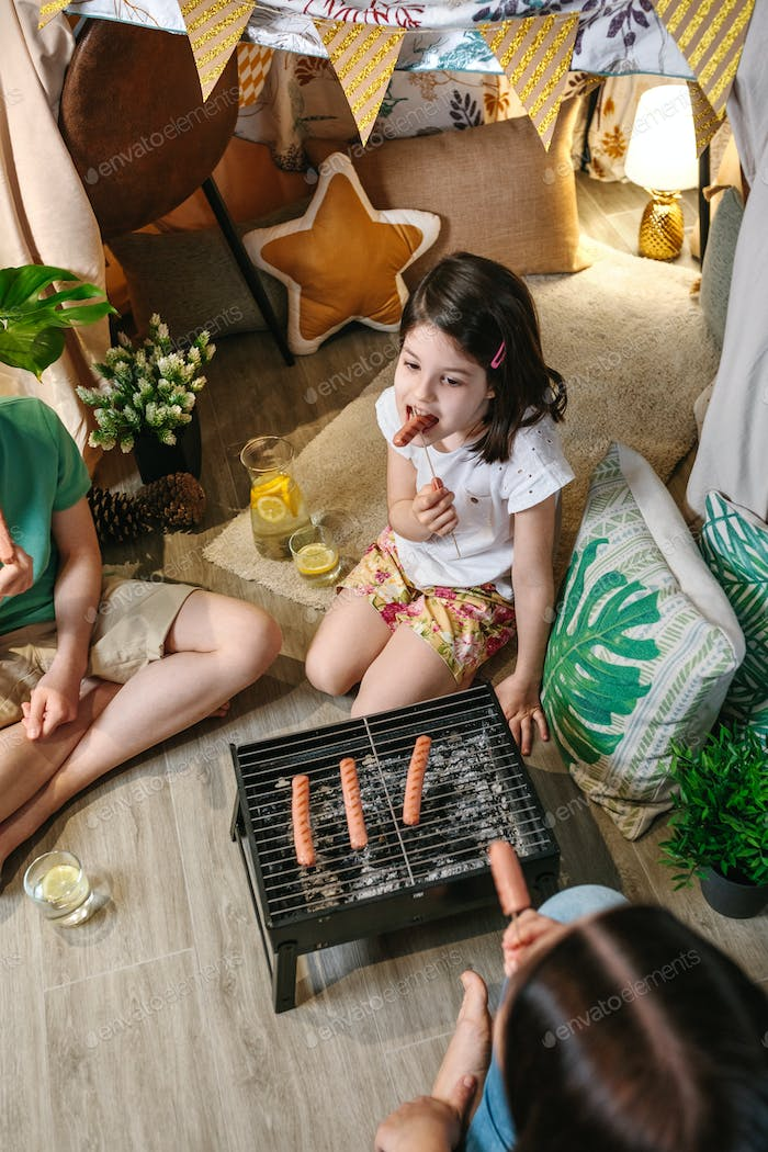 Top view of girl eating sausage with her family