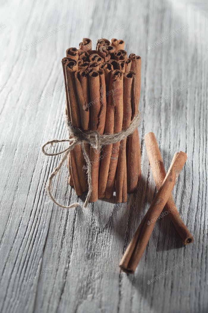 Cinnamon sticks isolated on white wooden table