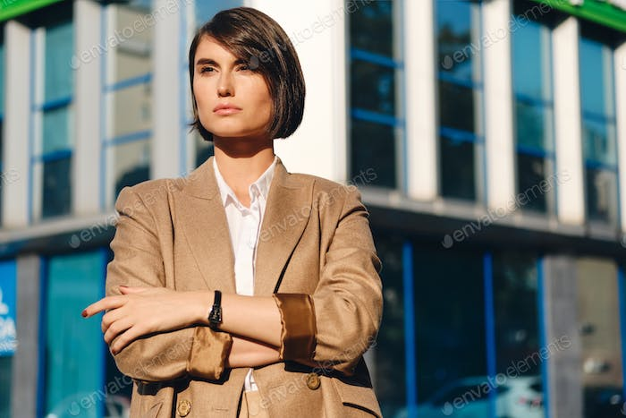 Young attractive businesswoman with crossed hands confidently looking away on street