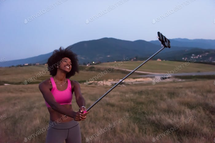 black woman photographing herself in nature