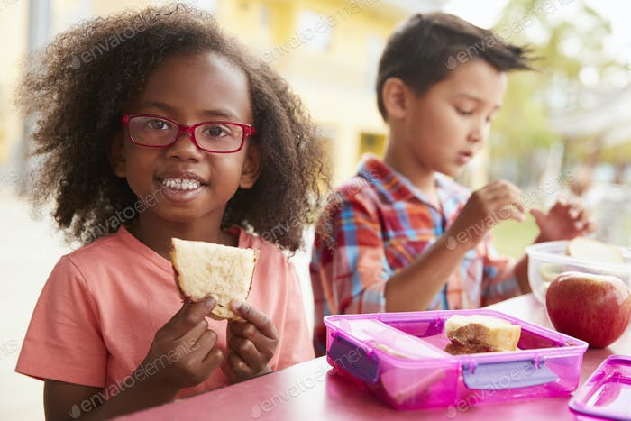 Young school girl and boy with packed lunches look to camera
