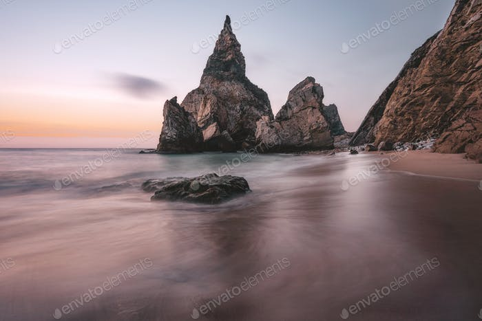 Rocky sea stacks at Portugal Ursa Beach at Atlantic Ocean coast in sunset light. Foamy waves rolling