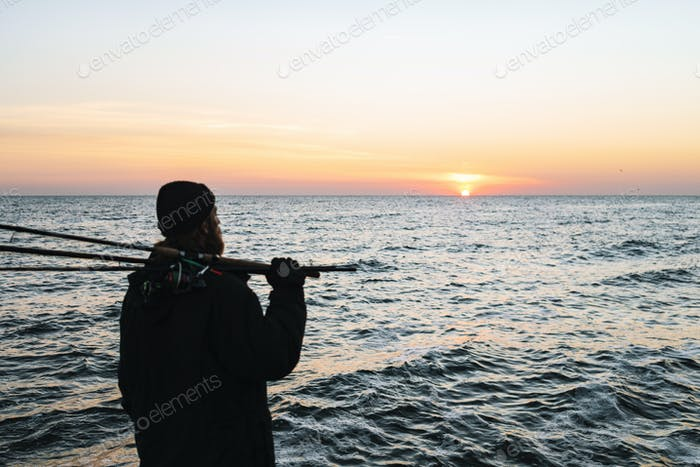 Silhouette of man fisherman wearing coat, holding rod