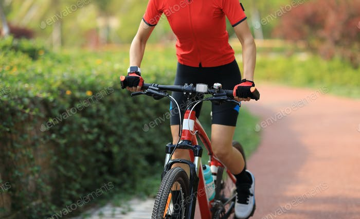 Woman biker riding bike in park