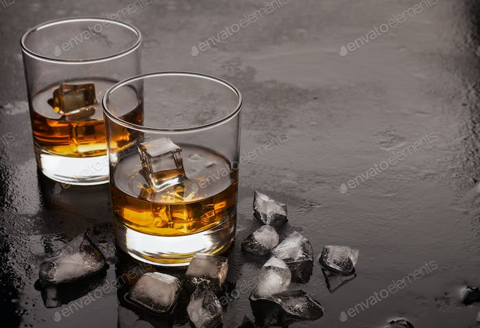 Two glasses of whiskey and ice on black background