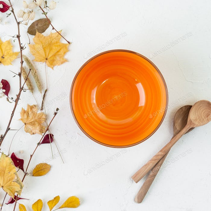 Bright orange empty bowl, wooden spoon and autumn leaves on a wh