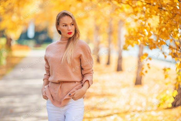 Beautiful woman in autumn park under fall foliage
