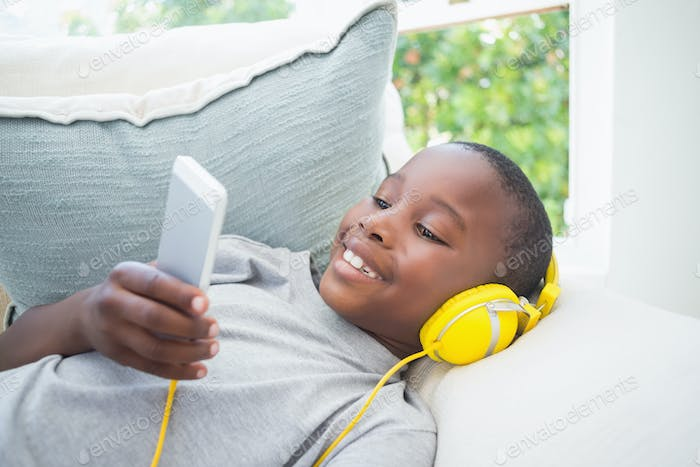 Little boy listening to music on the couch at home in the living room