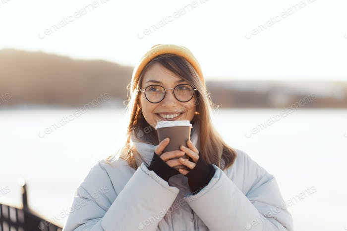 Happy young teenage woman holding a takeaway coffee cup