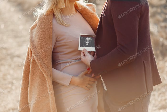 Pregnant woman standing in a park with her husband