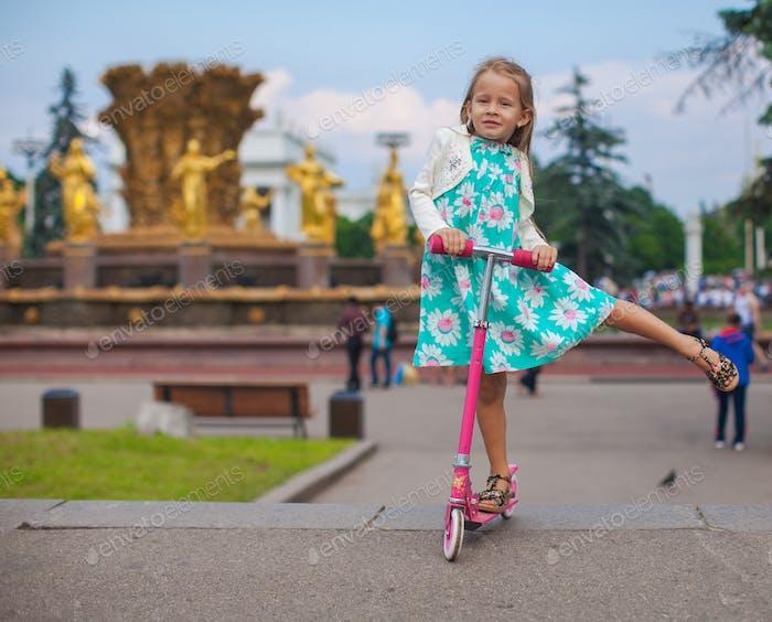 Fröhlich niedlich Kleinkind Mädchen auf dem Roller in einem Park