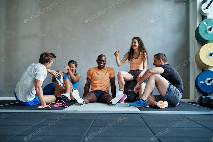 Diverse Gruppe von Freunden zusammen sitzen in einem Fitness-Studio lachen