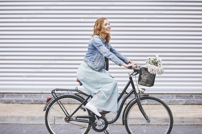 Happy adult woman enjoying the cycling