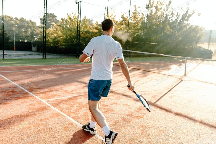 Man playing tennis in the morning in sunlight