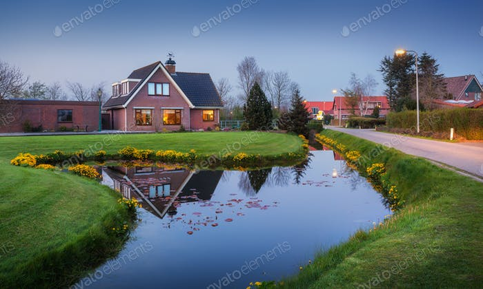 Landscape with beautiful house reflected in water canal at dusk