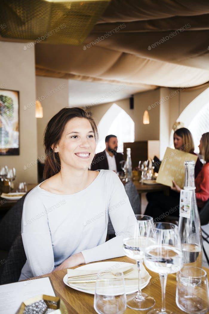 Glückliche Frau sitzt am Tisch im libanesischen Restaurant