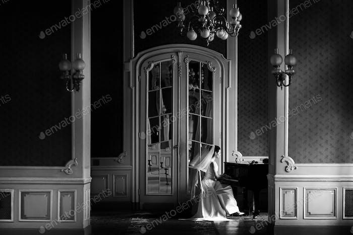 элегантная великолепная невеста играет фортепиано в богатой старой комнате