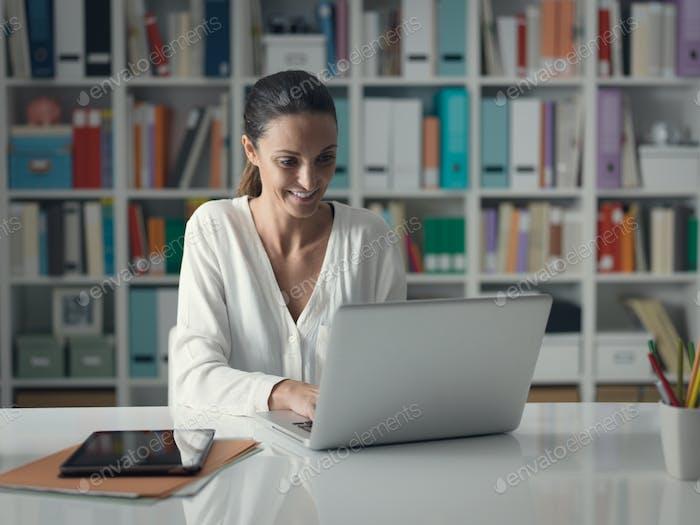 Frau, die sich zu Hause entspannt und sich mit einem Computer verbindet