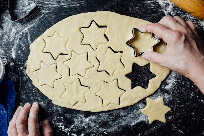 Cook making star-shaped cookies with form