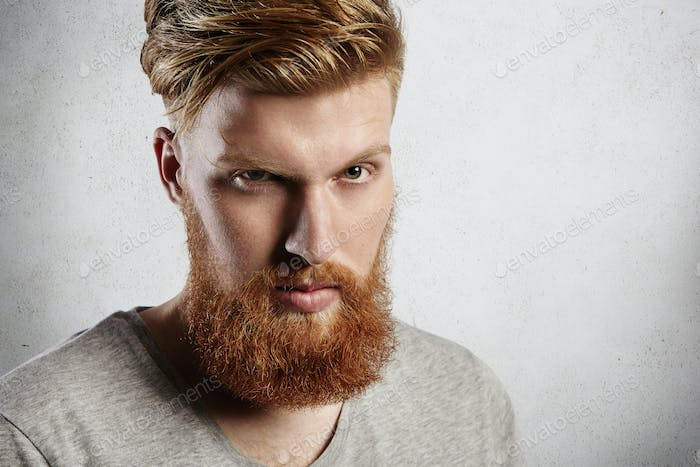 People and lifestyle. Headshot of handsome hipster with thick red beard and stylish hair looking at