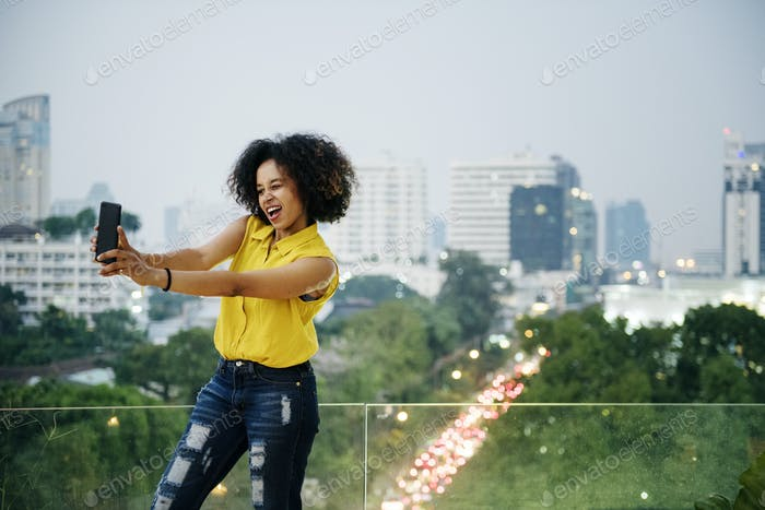 Young woman taking a cute selfie in the cityscape