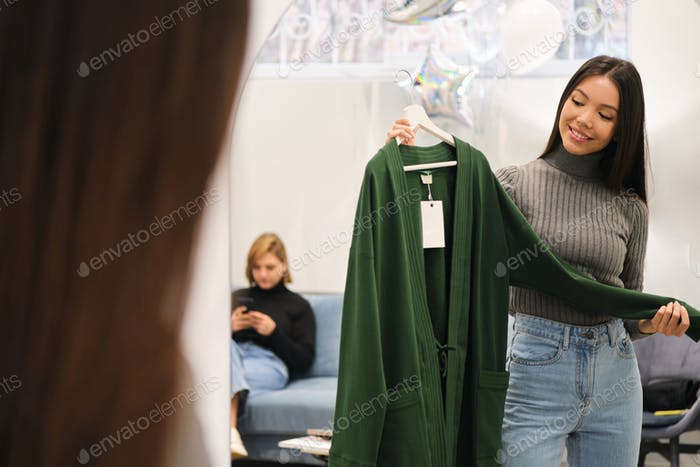 Attractive stylish Asian girl happily choosing cardigan in fashion store