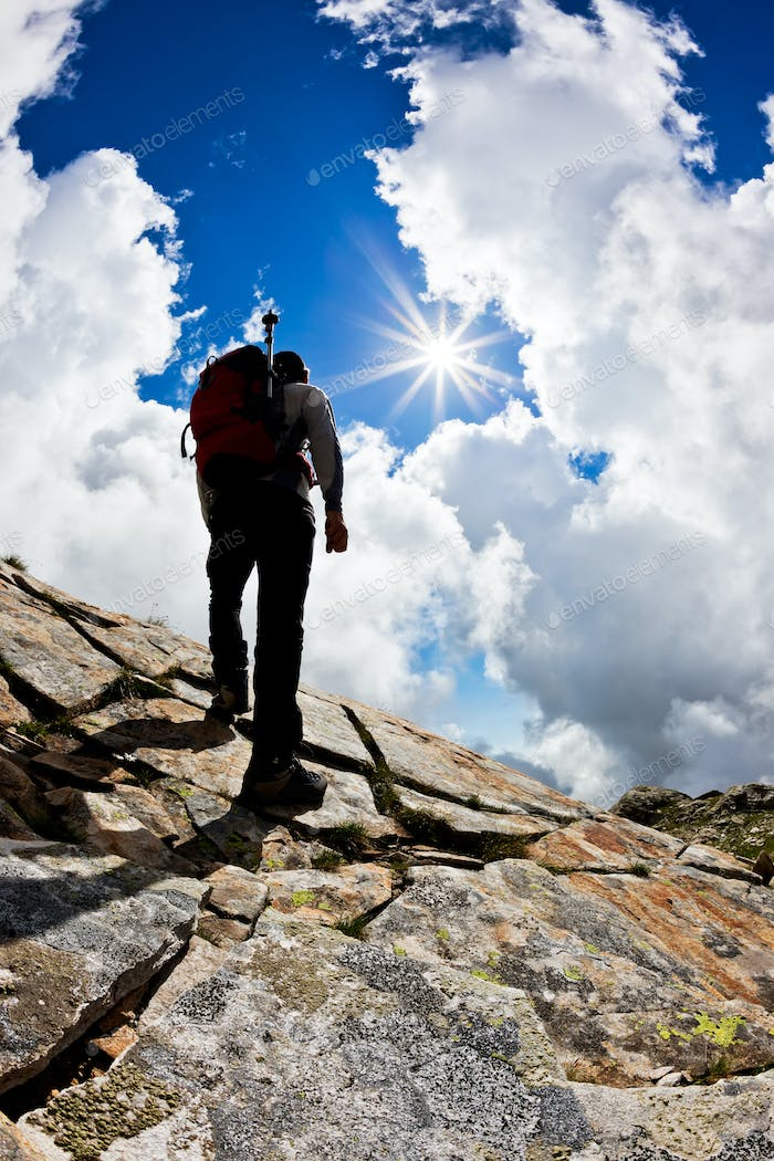 Rear view of a man hiking up a rock hill against a dramatic cloudy sky.