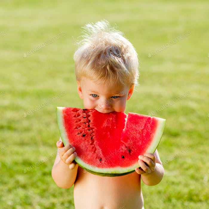 One year old baby boy eating watermelon in the garden