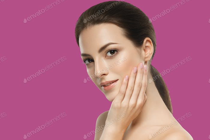 Beautiful brunette girl portrait  with hands for cosmetic concept over pink background.