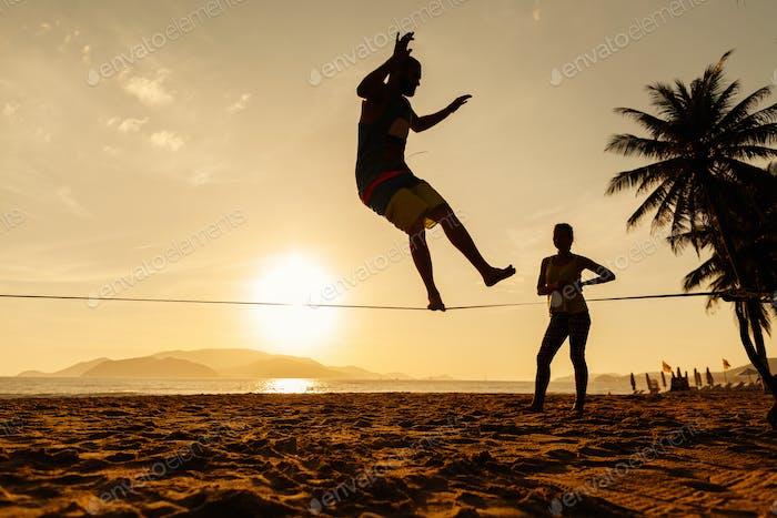 teenagers balance on slackline silhouette