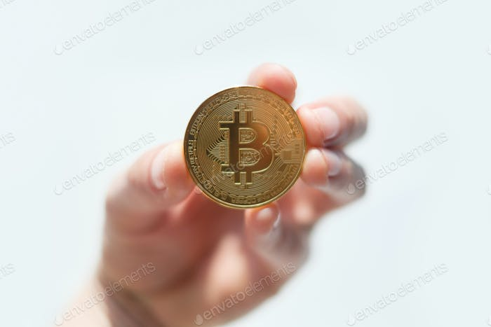 Golden bitcoin coin in man hand closeup